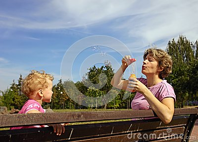 Mother and son blowing soap bubbles