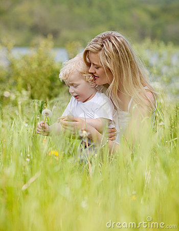 Mother and Son with Dandelion in Meadow