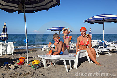 Mother, son and daughter sitting on beach