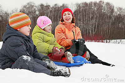 Mother, son and daughter sitting on snow
