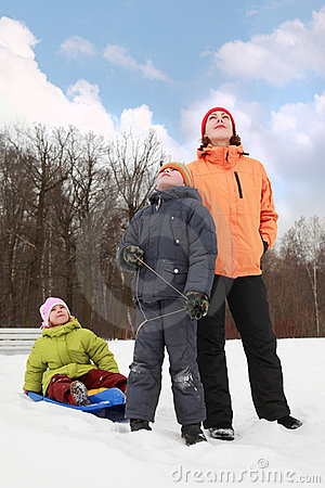 Mother, son and daughter standing on snow