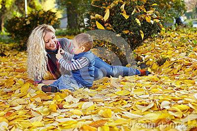 Mother and son on fallen leaves in autumn park