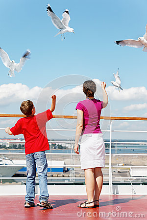 Mother and son feed seagulls on deck of ship.