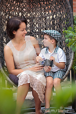 Mother and son having relax on cane-chair outdoors