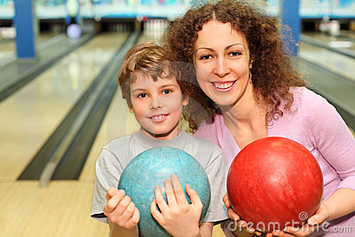 Mother and son keep balls in bowling club