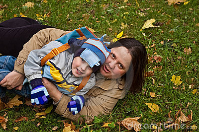 Mother and son lying on grass