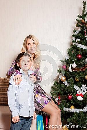 Mother with a son near a fir-tree