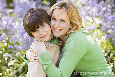 Mother and son outdoors embracing and smiling