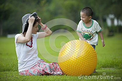 Mother and son play ball in grass