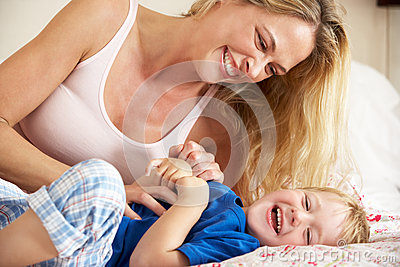 Mother And Son Relaxing Together In Bed