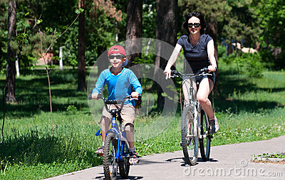 Mother and son riding bikes outdoors in summer