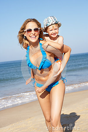 Mother And Son Running Along Beach