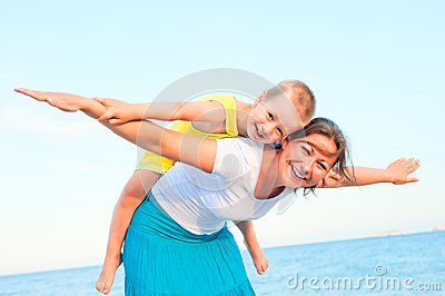 Mother and son sitting on her back, happy playing