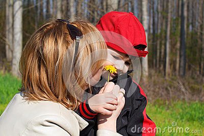 Mother and son smell dandelion