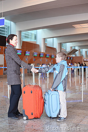 Mother and son with suitcases in airport hall