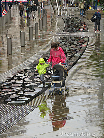 Mother and son walk in Manchester under rain Editorial Stock Image
