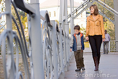 Mother and son walking  across the bridge