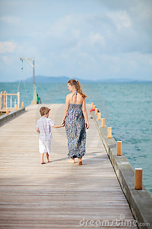 Mother and son walking along jetty