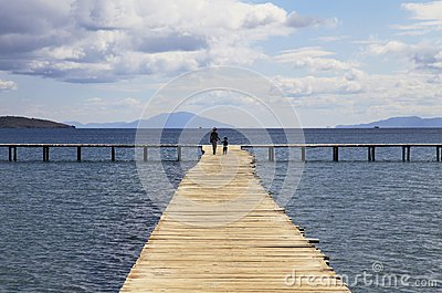 Mother and son walking on a wooden pier background with blue sky