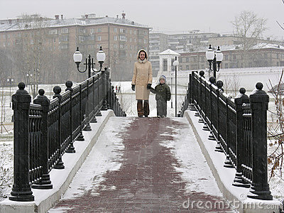 Mother with son on winter bridge