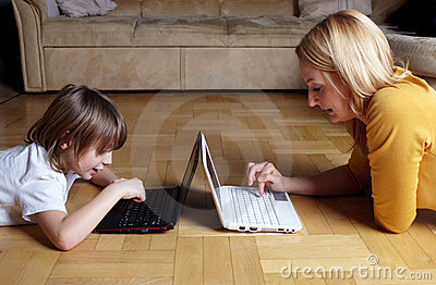 Mother and son working on two small laptops