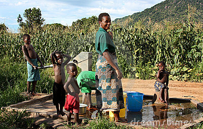 Mother and sons by a fountain in Africa Editorial Stock Image