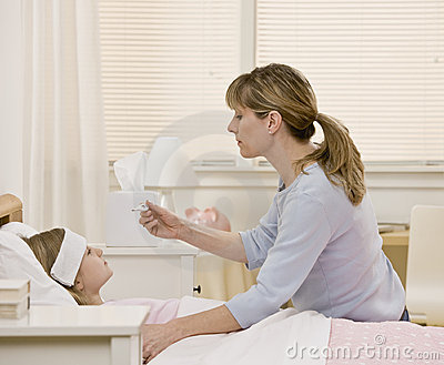 Mother taking ill daughter s temperature