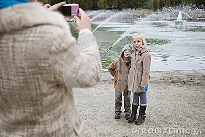 Mother taking photo of children in front of fountain