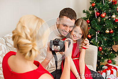 Mother taking picture of father and daughter