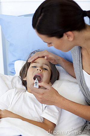 Mother taking son's temperature with a thermomet