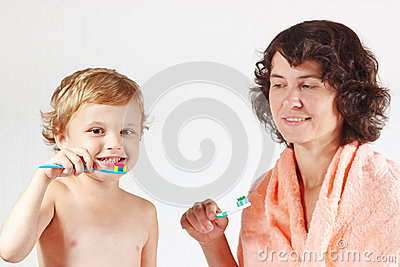 Mother teaches her little child to brush teeth