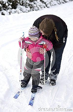 Mother teaching child to ski