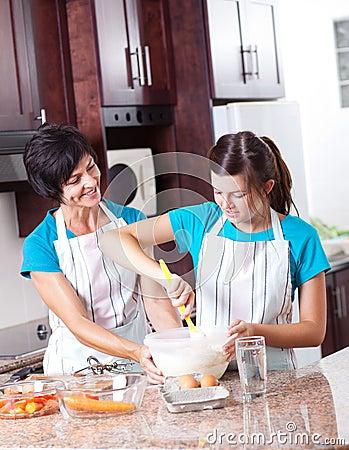 Mother teaching daughter baking