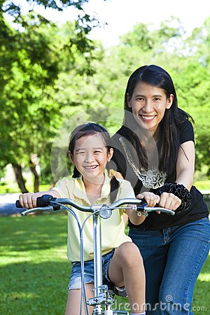 Mother Teaching daughter To Ride
