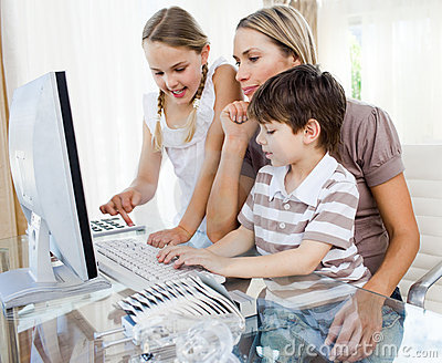 Mother teaching her children how to use a computer