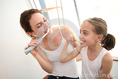 Mother teaching her daughter how to brush teeth Stock Photo