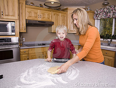 Mother teaching son to roll out dough