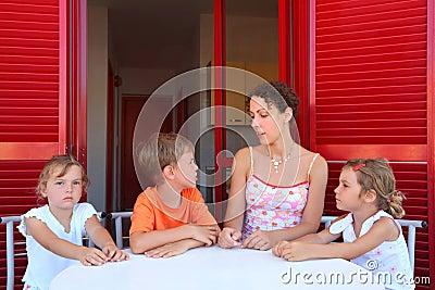 Mother and three children sit on verandah