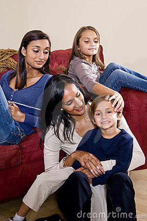 Mother and three children sitting at home together