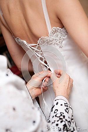Mother tie her daughter s wedding dress in white