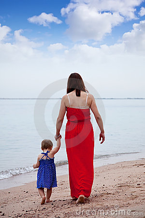 Mother with  toddler walking  on sand beach