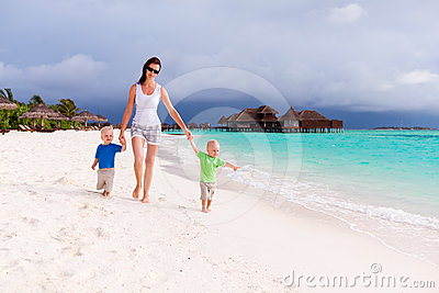Mother and two boys walking on tropical beach