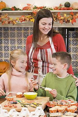 Mother and two children at Halloween making treats