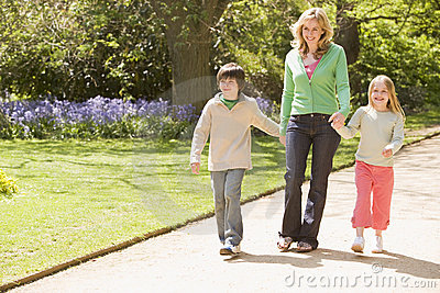 Mother and two young children walking on path