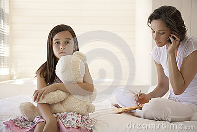Mother Using Cellphone With Daughter Holding Teddy Sitting On Bed
