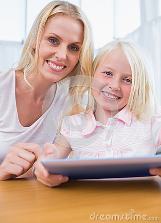 Mother using tablet pc with her daughter