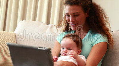 Mother Using Tablet Pc For Video Chat With Baby Son On Her Lap Stock