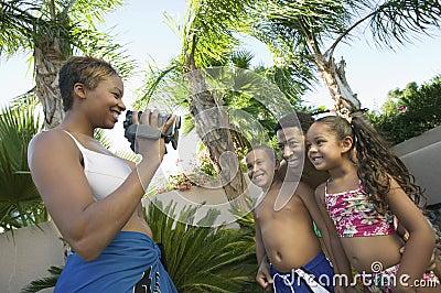 Mother Videotaping Family in swim wear in back yard side view