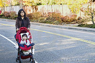 Mother walking with disabled son in stroller o
