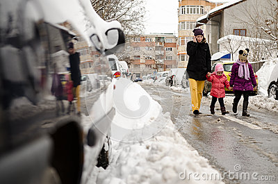 Mother walking with two children along snowy street Editorial Photography
